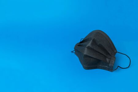 Black medical mask on blue background. Medical mask for protection against flu and other diseases and prevention of the spread of virus and epidemic. Banco de Imagens