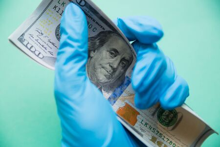 Hand in protective glove holds dollar. Financial crisis in USA because of the coronavirus concept. Focus on Benjamin Franklins eyes