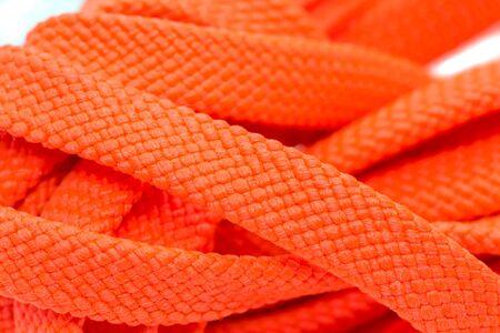 Orange shoelaces, isolated on a white background, close up.