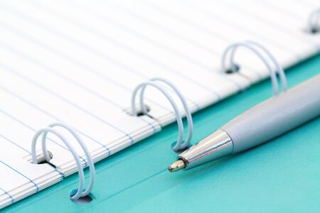 Opened lined paper notebook in a mint cover and ballpoint pen. Business, education and keep a diary concept. Copy space