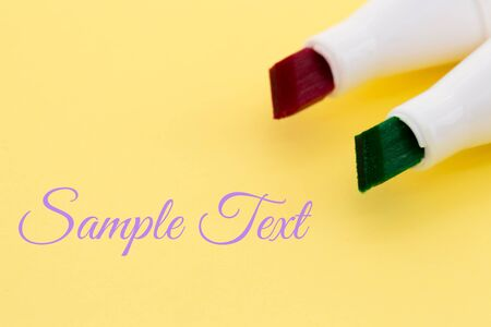 Colored markers - red and green, isolated on the yellow background with place for text Banco de Imagens