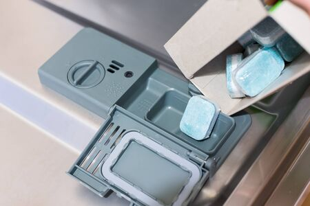 Man fills eco tablets detergent in dishwasher. Disposable tablets in plastic that dissolves.