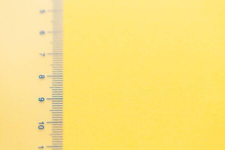 Transparent ruler with numbers on the yellow background. Measure concept. Left composition, copy space