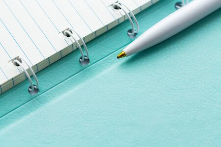Opened lined paper notebook in a mint cover and ballpoint pen. Business, education and keep a diary concept. Copy space.