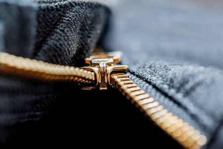 Close up image of a black denim jeans with its metal zipper or fly open and zipper tape metallic puller, bridge, slider body and chain visible along with brown stitching