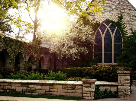 Picture of an old stone medieval church with a manicured front lawn and sun raises coming through the branch tree