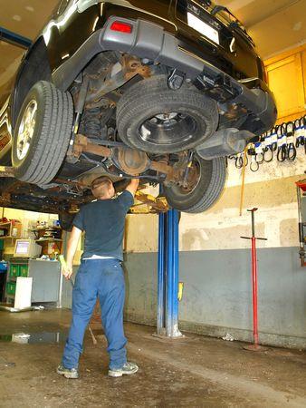 Auto mechanic working under a truck