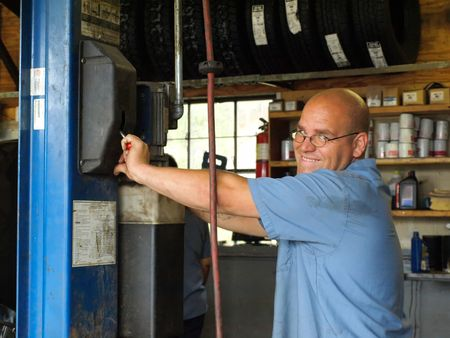 Free royalty stock photo of a happy mechanic pulling on a handle photo