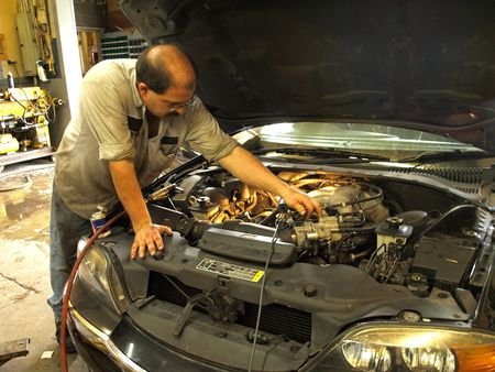 Stock photo of a mechanic working on a engine