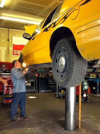 Royalty free stock photo of a car lifted up with a mechanic working on the tire Stock Photo