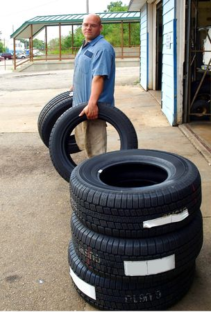photo of a auto mechanic carrying new auto tires Banco de Imagens