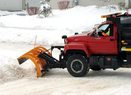 Red plowing truck clearing the roads of snow