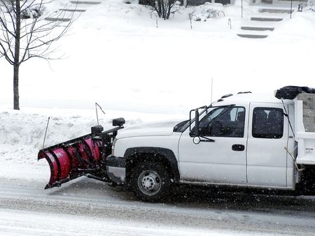 Stock image of a white truck with a red plow clearing the snow