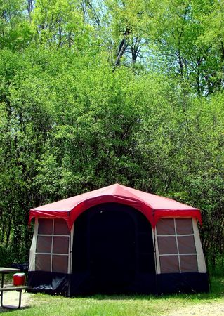 nylon: Photo of a red tent in the woods, on a sunny summer day