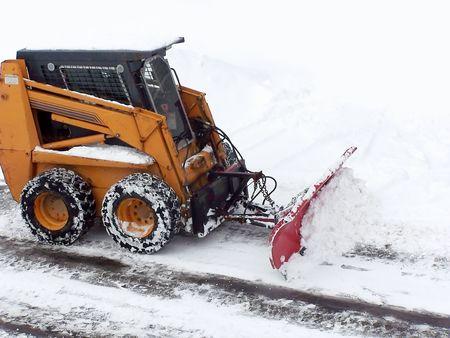 Royalty Stockfoto een mini bulldozer plowing de sneeuw