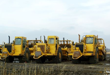 lined up: Photo of three yellow construction machines lined up on a muddy field, in a cloudy cold winter day