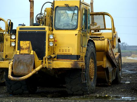 plow: Photography of a large yellow construction machinery on a muddy field