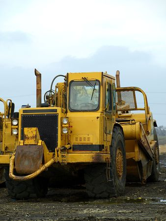 Photography of a large yellow construction machinery on a muddy field