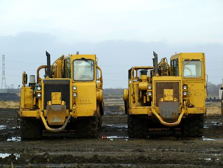 Picture of two huge construction machines on a muddy construction field