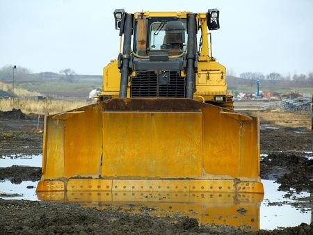 plow: Picture of a large caterpillar with a big plow on a muddy construction field on a winter day
