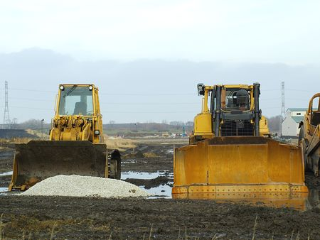 Photo of two yellow caterpillars with plows on a muddy construction field, on an overcast winter day