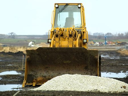 Stock illustration of a yellow caterpillar and a pile of white gravel on a muddy construction field