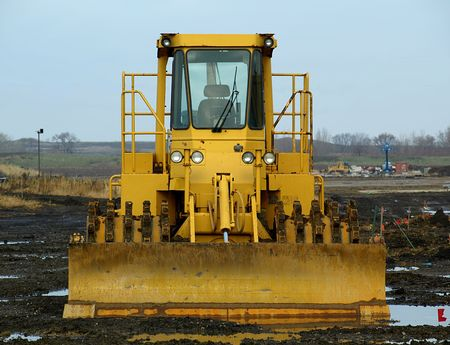 frontal: Stock photo of frontal view of a large caterpillar with plow on a construction field