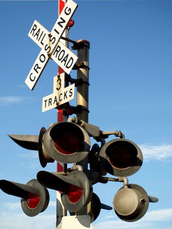 Royalty photo of a train signal at a roads intersection, against the blue sky photo
