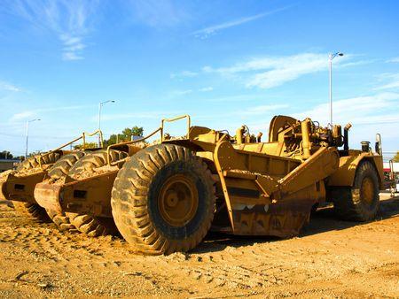 Foto von zwei riesige gelbe Baumaschinen auf einer Baustelle an einem sonnigen Tag mit blauem Himmel Standard-Bild - 3954450