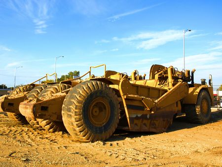 Photo of two huge yellow construction machines on a construction site on a sunny day with blue sky