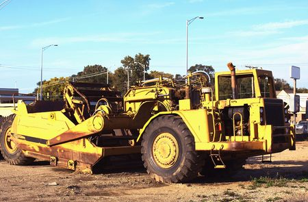 Photo of a huge yellow construction machine on a clay construction ground Stock Photo