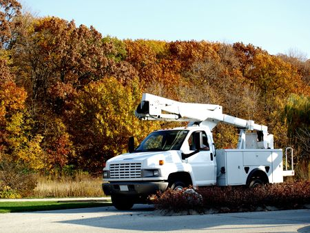 Photo of a diesel utility maintenance white truck with fall colored trees in the background