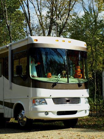 Stock royalty photo of the front of a motor home parked on a camp ground with the dashboard decorated for Halloween Stock Photo