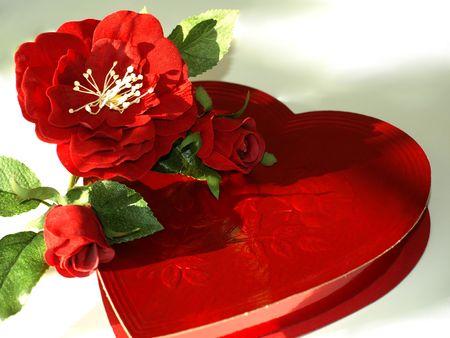 Foto de un corazón rojo en forma de caja de chocolates con rosas rojas de seda