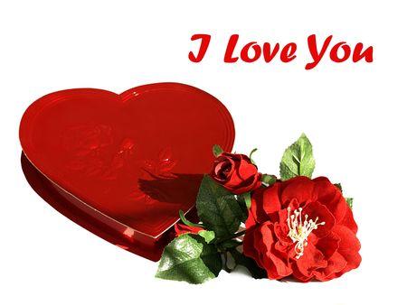 Foto de un corazón rojo en forma de caja de chocolates con rosas de seda roja y el texto Te amo, en una fuente distinta