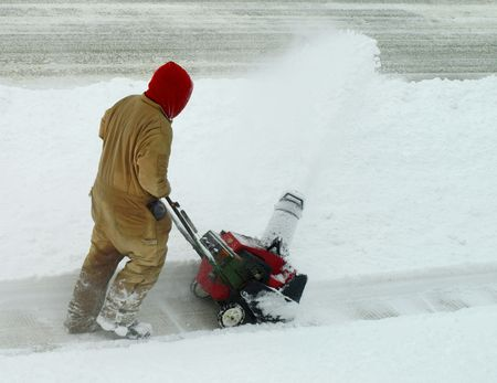clearing the path: Man with snow blower