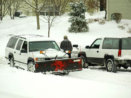 Picture of a man between tow white plowing trucks on a snowy day photo