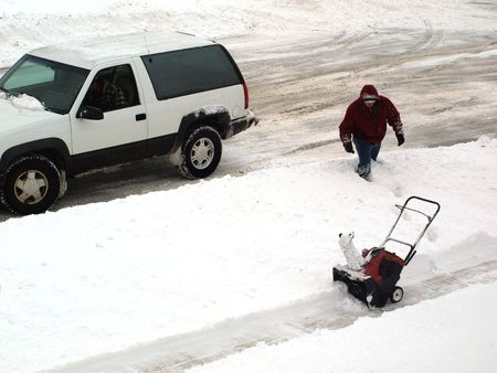 Photo of a man walking in the snow to his snow blower from a snow plow truck photo
