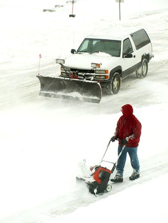 Picture of a man in red jacket blowing the snow and a white truck plowing the snow photo