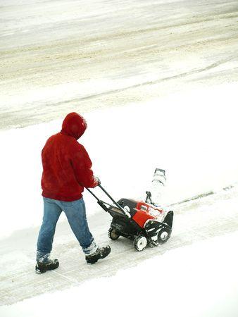 hombre empujando: Foto de un hombre empujando el soplador de nieve Foto de archivo