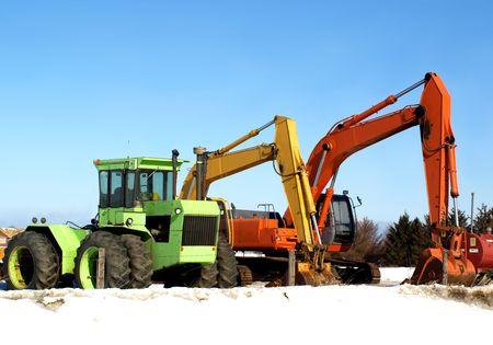 Stock photo of three excavators on a construction site, in sunny winter day
