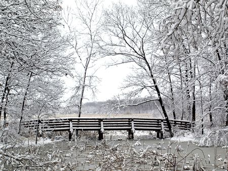 Royalty free photo of a snowy wood bridge in the park Stock Photo