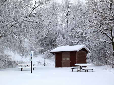Photo of a rural public restroom and a picnic table in a park, photo taken on a cold winter and snowy day