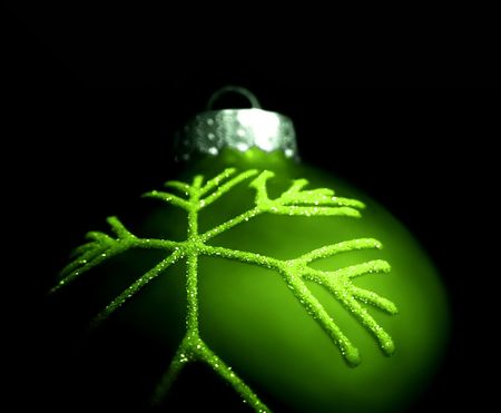 Graphic illustration, closeup of a single green tree ornament, bulb, isolated over black