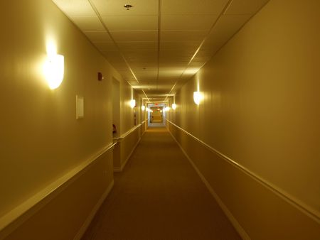 Picture of a very long and simple hallway with many doors and wall light sconces