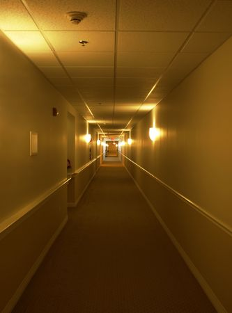sconces: Picture of a very long and simple hallway with many doors and wall light sconces