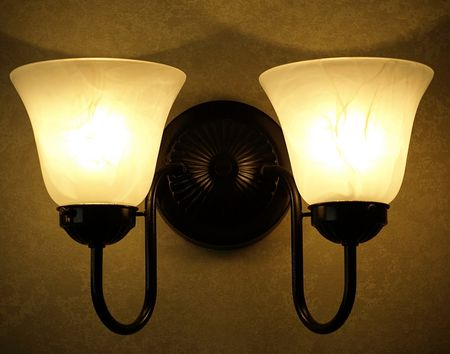 light fixture: Image of a wall light fixture with two arms and two frosted lamp shades  Stock Photo