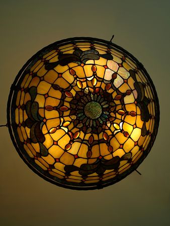 style: Photo of a beautiful lit Tiffany style ceiling lamp in warm and bright colors Stock Photo