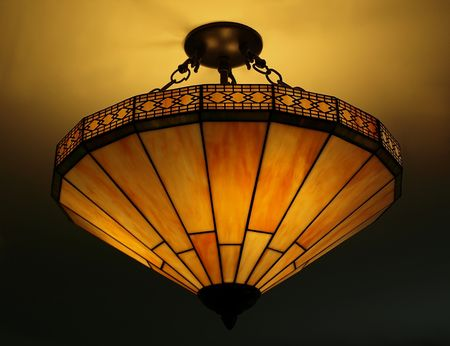Photo of a beautiful lit Tiffany style ceiling lamp in warm and bright colors photo