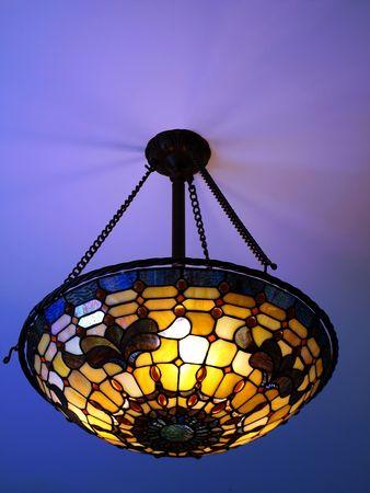 Foto van een mooie verlichte Tiffany stijl plafond lamp in warme en heldere kleuren, in een helder blauwe plafond
